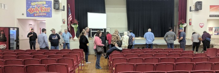 A line of people in front of the stage in a middle school auditorium talk to each other and look at copies of historical documents. Red auditorium seating fills the foreground.